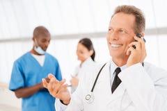 Doctor alegre en el teléfono Fotos de archivo libres de regalías