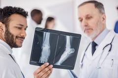 Doctor alegre que demuestra la radiografía en clínica fotos de archivo