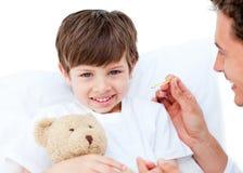 Doctor alegre que toma la temperatura del niño pequeño Imagen de archivo libre de regalías