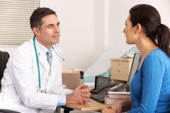 Doctor americano que habla con la mujer en cirugía Fotos de archivo