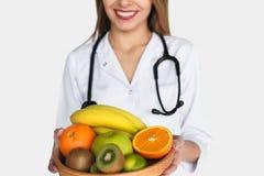 Doctor anónimo que presenta con las frutas fotografía de archivo