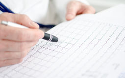 Doctor analyzing electrocardiogram Royalty Free Stock Image