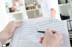 Doctor analyzing an electrocardiogram Stock Photography