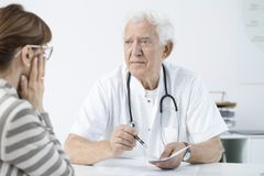 Doctor announcing bad news. Worried doctor announcing bad news to his patient after medical examination Royalty Free Stock Images