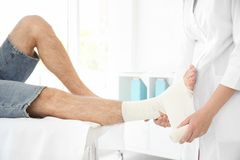 Doctor applying bandage onto patient`s leg royalty free stock photos