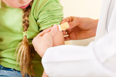 Doctor applying bandage - Pediatrician. Doctor in her practice putting a bandage on some hurt of a little girl child (focus on thumb of doctor Stock Photography