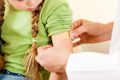 Doctor applying bandage - Pediatrician. Doctor in her practice putting a bandage on some hurt of a little girl child (focus on patch Royalty Free Stock Photos