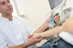 Doctor applying lubricating gel to patient`s arm Stock Image