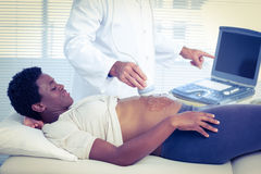 Doctor applying ultrasound gel on belly of woman Stock Images