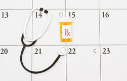 Doctor Appointment. A pill bottle and a stethoscope on a calendar background, doctor appointment stock photography