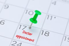 Doctor appointment on a calendar with a green push pin to remind royalty free stock image