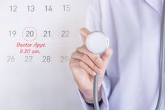 Doctor appointment concept background with note on calendar and doctor hand holding stethoscope royalty free stock images
