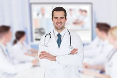 Doctor with arms crossed against team video conferencing Stock Images