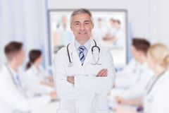 Doctor with arms crossed in meeting room Royalty Free Stock Photo