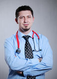 Doctor with Arms Crossed. Portrait of a handsome young doctor standing with his arms crossed Stock Images