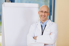 Doctor With Arms Crossed Standing By Flipchart Royalty Free Stock Photos