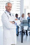 Doctor with arms crossed. Standing in front of medical team Stock Photo