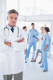 Doctor with arms folded in front of his medical team Royalty Free Stock Image