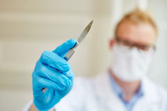 Doctor as surgeon with scalpel. And gloves during surgery Royalty Free Stock Photo