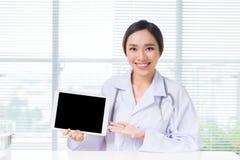 Doctor asiático de la mujer que muestra la pantalla digital de la tableta imágenes de archivo libres de regalías