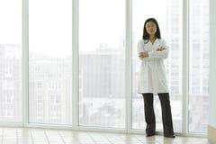 Doctor asiático de sexo femenino que se coloca con los brazos cruzados Imagenes de archivo