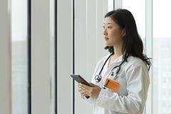 Doctor asiático de sexo femenino que sostiene una tableta Fotos de archivo libres de regalías