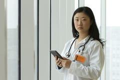 Doctor asiático de sexo femenino que sostiene una tableta Imagen de archivo libre de regalías