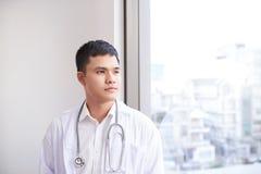 Doctor asiático de sexo masculino joven que mira fuera de la ventana el hospital imágenes de archivo libres de regalías