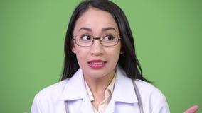 Doctor asiático hermoso joven de la mujer que parece chocado almacen de video
