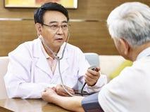 Doctor asiático que comprueba la presión arterial de un paciente mayor Foto de archivo libre de regalías