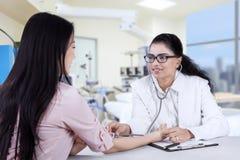 Doctor asiático que escucha el latido del corazón paciente Imagen de archivo libre de regalías