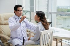 Checkng throat. Doctor asking female patient to open mouth so he could check her throat Royalty Free Stock Images