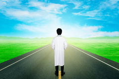 Doctor with asphalt road through the field with sky Royalty Free Stock Image