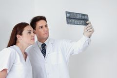 Doctor And Assistant Analyzing Patient's Report Royalty Free Stock Image