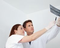 Doctor And Assistant Analyzing Patient's Report Royalty Free Stock Photos