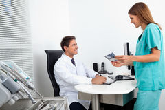 Doctor And Assistant With Dental Report Stock Image