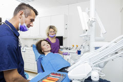 Doctor And Assistant Examining Patient At Dentistry Royalty Free Stock Images