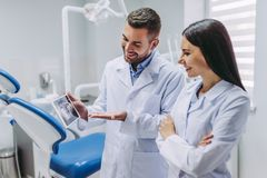 Doctor and assistant looking at tablet screen stock image