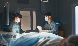 Doctor and an assistant in operating room for surgical  clinic. Doctor and an assistant in the operating room for surgical venous vascular surgery clinic Royalty Free Stock Photos