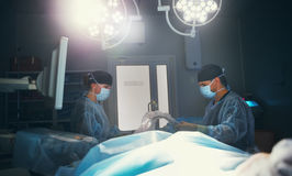 Doctor and assistant preparing for surgery in operating room. Doctor and assistant preparing for surgery in the dark operating room with a dark lamp Stock Photography