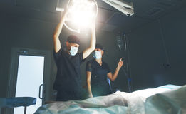 Doctor and assistant preparing for surgery in operating room. Doctor and assistant preparing for surgery in the dark operating room with a dark lamp Royalty Free Stock Photography