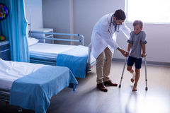 Doctor assisting injured boy to walk with crutches. In hospital Royalty Free Stock Images