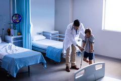 Doctor assisting injured boy to walk with crutches. In hospital Stock Image