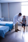 Doctor assisting injured boy to walk with crutches Stock Images