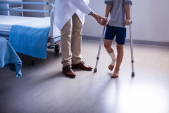 Doctor assisting injured boy to walk with crutches. In hospital Stock Images