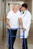 Doctor Assisting Old Man On a Walker Stock Photos