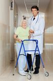 Doctor Assisting An Old Woman With Her Walker Stock Photo