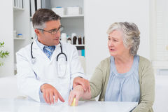 Doctor assisting patient to hold weight at table Royalty Free Stock Image