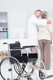 Doctor assisting senior woman to walk with wheelchair in foreground Stock Image