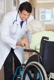 Doctor Assisting Senior Woman In Wheelchair Stock Images
